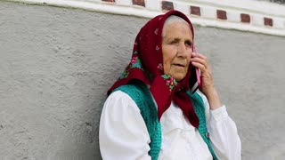 Old woman sits near his house and speaks on mobile phone. Female with smartphone. Ukrainian old woman with red smartphone