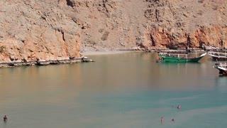 OMAN, MUSANDAM PENINSULA, GULF OF OMAN, FEBRUARY 2, 2016: People in sea near pleasure ship near coast of Musandam peninsula. Sultanate of Oman - arab country in southeastern coast of Arabian Peninsula