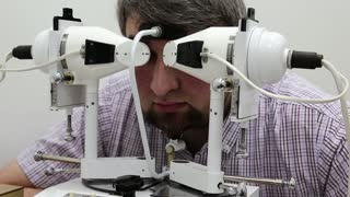 Patient in ophthalmology clinic. Man looks in synoptophore - ophthalmic Instrument, used for diagnosing imbalance of eye muscles and treating them by orthoptic methods, for treatment of strabismus