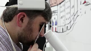 Patient in ophthalmology clinic. Man looks inside apparatus for magnetic therapy in ophthalmologist office, magnets on the head