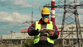 Power engineering specialist in respirator and yellow hard hat with personal computer in hands at heat power plant. Powerman in gas mask with tablet computer on electric power station
