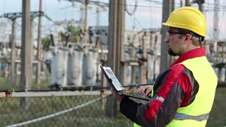 Power engineering specialist with personal computer at electric power station. Worker in yellow hard hat at electric station, engineering supervision. Factory worker with tablet pc