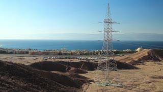 Power transmission tower near Tala Bay resort near Aqaba city in Hashemite Kingdom of Jordan. View on overhead power line, Red Sea, Gulf of Aqaba and Tala Bay resort