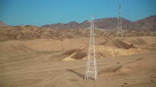 Power transmission towers in desert in Jordan. Overhead power line
