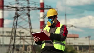 Powerman in gas mask on electric power station makes notes in his work papers. Power engineering specialist on heat power plant in respirator and yellow hard hat writes in documents