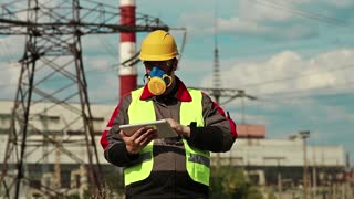 Powerman in gas mask with tablet computer on electric power station. Power engineering specialist in respirator and yellow hard hat with personal computer in hands at heat power plant