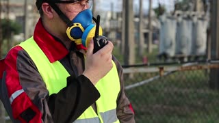 Powerman in respirator and with portable radio transmitter on electric power station. Power engineering specialist in gas mask, goggles and hard hat on heat power plant communicates via radio station