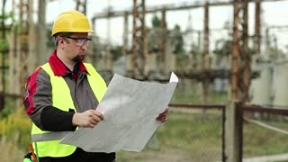 Powerman with scheme of works on power station. Worker with construction documentation at power plant. Master builder in hard hat and with design drawings