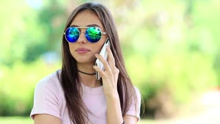 Pretty woman in glasses talks on the mobile phone in public garden. Beautiful woman in sunglasses talks on the cell phone. Attractive girl speaks on smartphone in city park