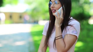Pretty woman speaks on cell phone. Beautiful girl in glasses talks on the mobile phone, female with white smartphone