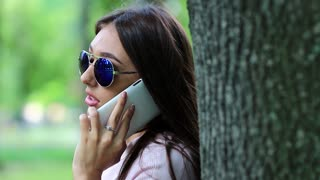 Pretty woman with long hair stands near the tree and speaks on cell phone. Attractive girl speaks on cell phone. Businesswoman with smartphone on the nature