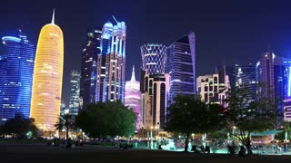 QATAR, DOHA, MARCH 20, 2018: People in public park near skyscrapers in financial district in Doha - capital and most populous city in Qatar, Corniche road, Persian Gulf, Arabian Peninsula, Middle East