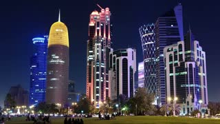 QATAR, DOHA, MARCH 20, 2018: People on lawn near skyscrapers in financial district in Doha - capital and most populous city in Qatar, Corniche road, West Bay, Persian Gulf,Middle East