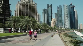 QATAR, DOHA, MARCH 20, 2018: People walks on Corniche road in Doha - capital and most populous city in Qatar, Persian Gulf, Arabian Peninsula, Middle East. View on skyscrapers in Doha downtown