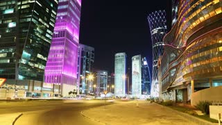 QATAR, DOHA, MARCH 20, 2018: UHD 4K night time lapse of road traffic in financial centre near NOC and pink Al-Asmakh Towers in Doha - capital and most populous city in Qatar