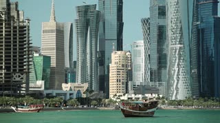 QATAR, DOHA, MARCH 20, 2018: View on financial district and dhow - traditional wooden Qatari boat, Doha Bay, Qatar, Persian Gulf, Arabian Peninsula. Doha - capital and most populous city in Qatar