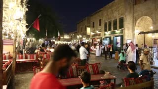 QATAR, DOHA, MARCH 22, 2018: People at restaurant in Souq Waqif or the standing market - eastern bazaar in Doha - capital and most populous city in Qatar, Persian Gulf, Arabian Peninsula
