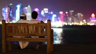 QATAR, DOHA, MARCH 22, 2018: Two Muslim guys sits on bench and looks at skyscrapers in financial district in Doha - capital and most populous city in Qatar, Persian Gulf, Arabian Peninsula, Middle East