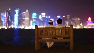 QATAR, DOHA, MARCH 22, 2018: Two Muslim guys sits on bench and looks at skyscrapers in financial district in Doha - capital and most populous city in Qatar, Persian Gulf, Arabian Peninsula,Middle East