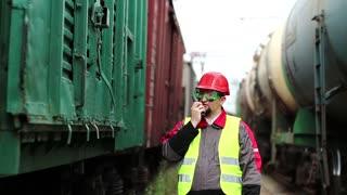 Railroader with portable radio transmitter near goods trains. Railway employee on railway line near freight station speaks via portable radio transmitter, worker communicates via radio station