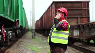 Railway employee in working clothes on railway line speaks on mobile phone, manager of works communicates via smartphone on freight station. Railwayman talks on cell phone near goods train