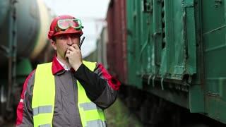 Railway employee on railway line near freight station speaks via portable radio transmitter, worker communicates via radio station. Railroader with portable radio transmitter near goods trains