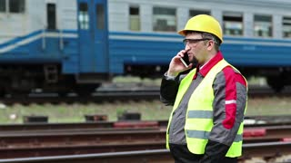 Railway employee speaks on cell phone. Railway worker stands on railway line and talks on mobile phone, railroadman communicates via smartphone on freight station