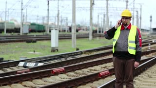 Railway employee speaks on mobile phone. Railway worker stands on railway line and speaks on mobile phone, manager of works communicates via smartphone on freight station