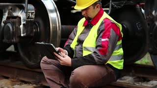 Railway employee with tablet pc sits on rail near big metal wheel of wagon. Railway worker with personal computer. Railwayman on freight station makes notes in his tablet computer