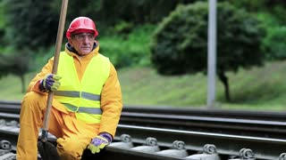 Railway man sits on the rails and looks at the train. Workman with spade on railway track. Railway construction, worker in yellow uniform with shovel in hand sits on railway line