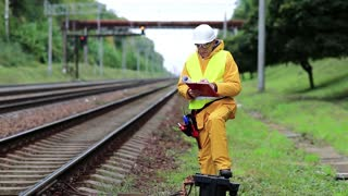 Railway worker in yellow uniform and white hard hat with documents in hands. Inspector of railway traffic makes notes in his documents. Railway employee in yellow uniform on railway line