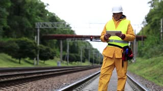 Railway worker in yellow uniform and white hard hat with tablet pc in hands. Railway worker makes notes in his tablet computer. Railway employee in yellow uniform on railway line