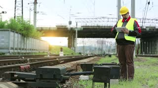 Railway worker makes notes in his tablet pc. Railway employee with tablet computer stands on railway line. Service technician in yellow hard hat works with tablet computer