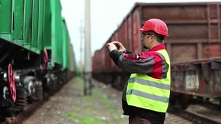 Railway worker stands on railway line on freight station and records video on cell phone. Railwayman records video on smartphone