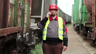 Railway worker talks on cell phone near moving goods train. Railway employee in working clothes on railway line speaks on mobile phone, manager of works communicates via smartphone on freight station