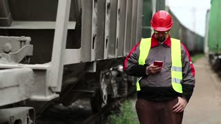 Railway worker talks on mobile phone near goods trains. Railway employee in working clothes between goods trains speaks on mobile phone, manager of works communicates via smartphone on freight station