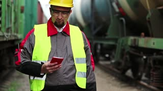 Railway worker talks on mobile phone near goods trains. Railway employee in working clothes on railway line speaks on mobile phone, manager of works communicates via smartphone on freight station