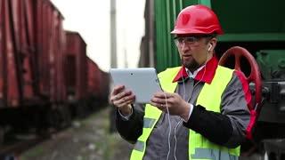 Railway worker talks via tablet computer between goods train. Railwayman on freight station talks through video chat via tablet pc
