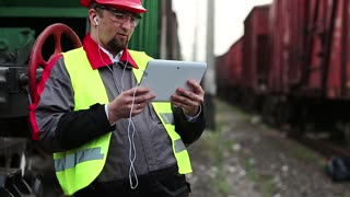 Railway worker talks via tablet computer between goods train. Railwayman on freight station talks through video chat via tablet pc