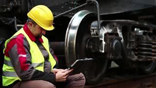 Railway worker with personal computer. Railwayman on freight station makes notes in his tablet computer. Railway employee with tablet pc sits on rail near big metal wheel of wagon