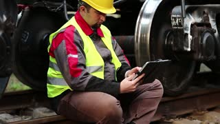 Railway worker with personal computer. Railwayman with tablet pc sits on rail near big metal wheel of wagon. Railway worker on freight station makes notes in his tablet computer