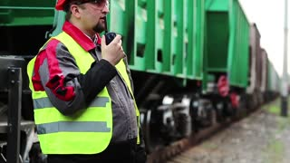Railway worker with portable radio transmitter near goods trains. Railway employee on railway line near freight station speaks via portable radio transmitter, worker communicates via radio station