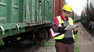 Railway worker with work documentation. Railroadman in hard hat with work scheme in hands. Inspector of railway traffic on freight station makes notes. Railway employee between goods trains