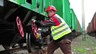 Railwayman at work. Railway worker stands near wagon of goods train on freight station and turns red wheel