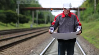 Railwayman in white hard hat with work scheme in hands. Railway worker with design drawings in hands stands on rail branch