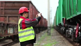 Railwayman records video on smartphone. Railway worker stands on railway line on freight station and records video on cell phone