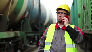 Railwayman talks on cell phone near goods train. Railway employee in working clothes on railway line speaks on mobile phone, manager of works communicates via smartphone on freight station