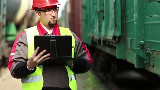 Railwayman with computer at freight train terminal. Railroadman in uniform and red hard hat works with tablet computer. Railway employee makes notes in his tablet pc