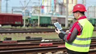 Railwayman with computer at freight train terminal.Railwayman in uniform and red hard hat works with tablet computer. Railway employee makes notes in his tablet pc