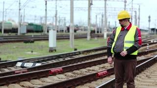 Railwayman with portable radio transmitter near railway terminal. Railway employee on railway line near freight station talks via portable radio transmitter, worker communicates via radio station